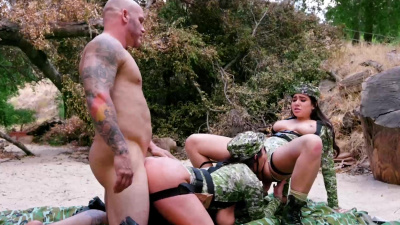 Angela White and Karlee Grey in camo outfits take turns on dick outdoors